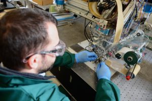 Figure 2: A researcher adjusts the wide tape continuous tow steering (CTS) machine head